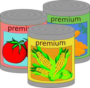A yellow can of corn in the front, a red can of tomatoes behind the corn and to the left and a green and blue can of carrots behind the tomatoes and to the right.